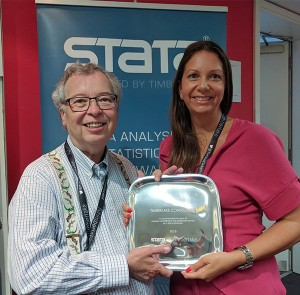 Teresa Timberlake accepting a presentation from Bill Gould, President of StataCorp at 2016 London Stata Users Group Meeting